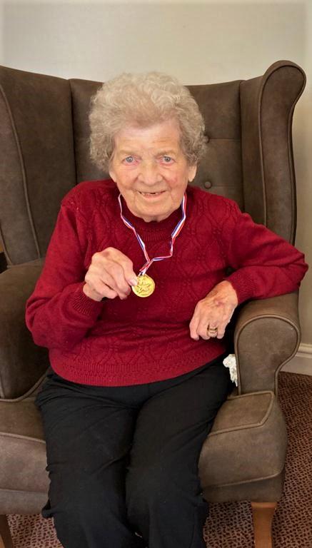 New resident, Beryl holding medal